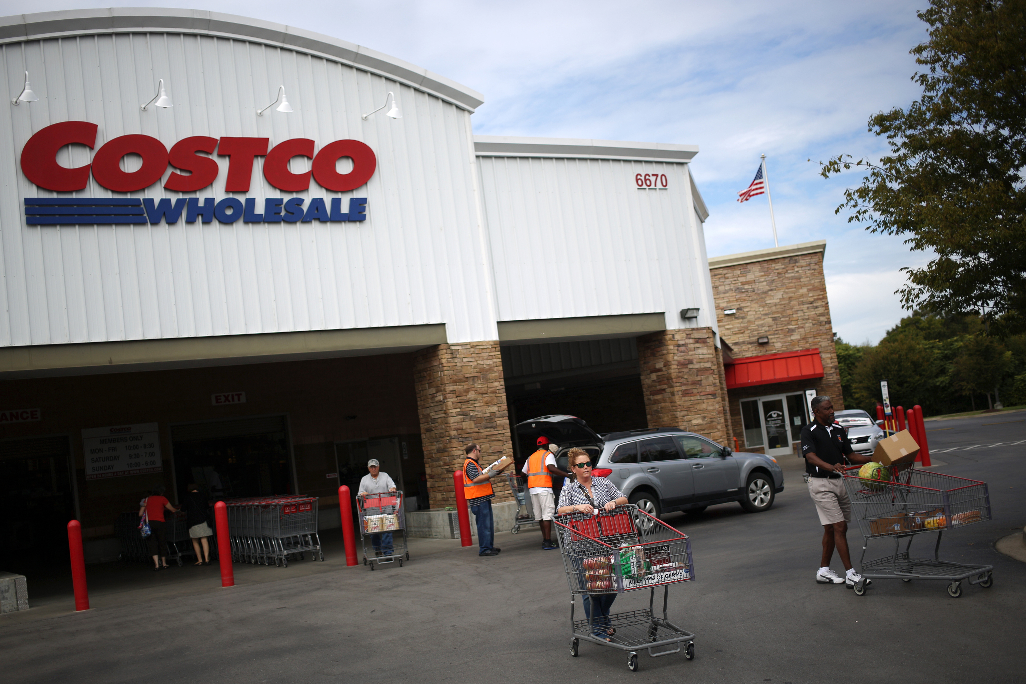 customers push carts through a parking lot after shopping at a costco wholesale corp store