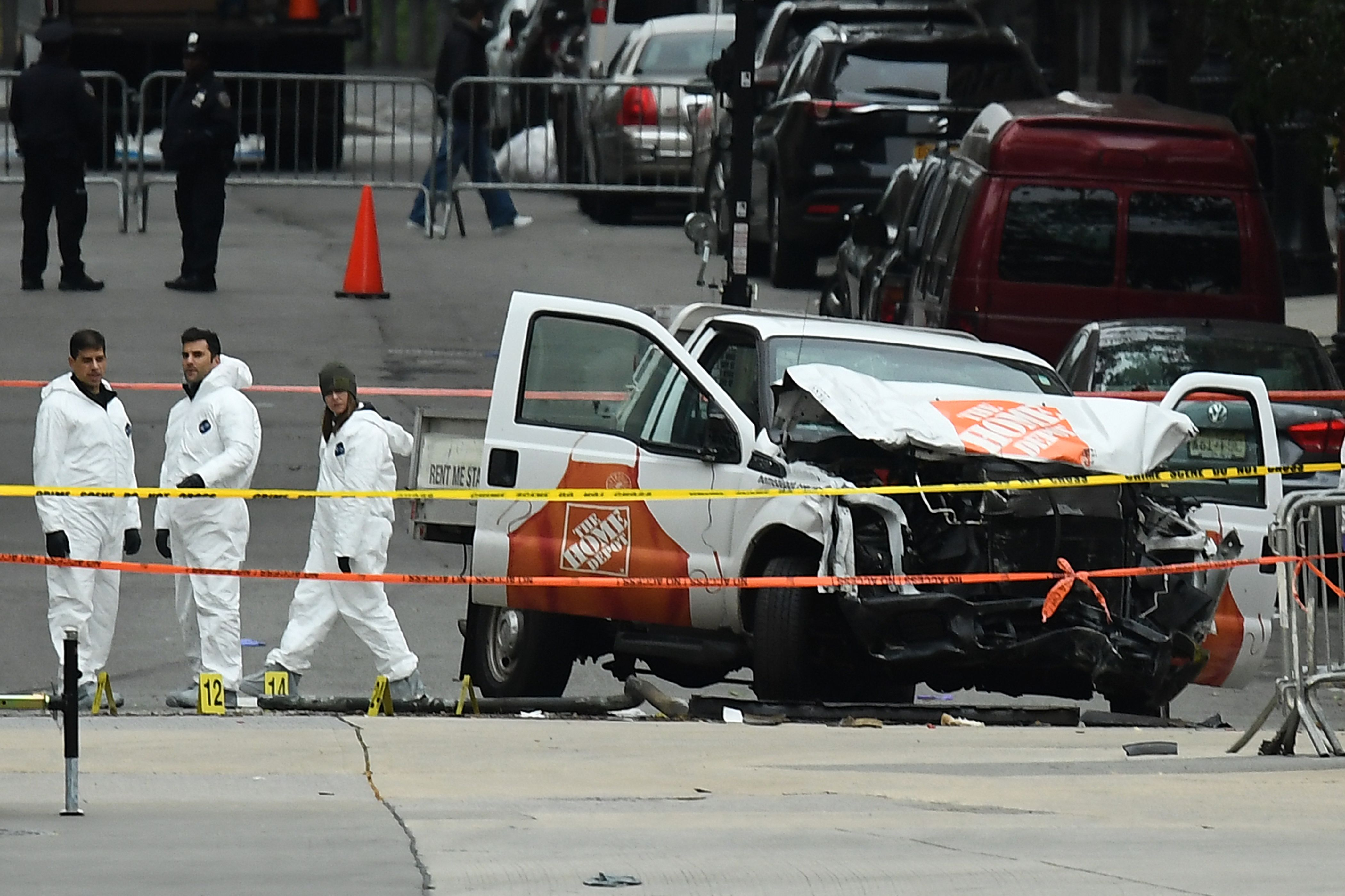 investigators work around the wreckage of a home depot pickup truck a day after it was