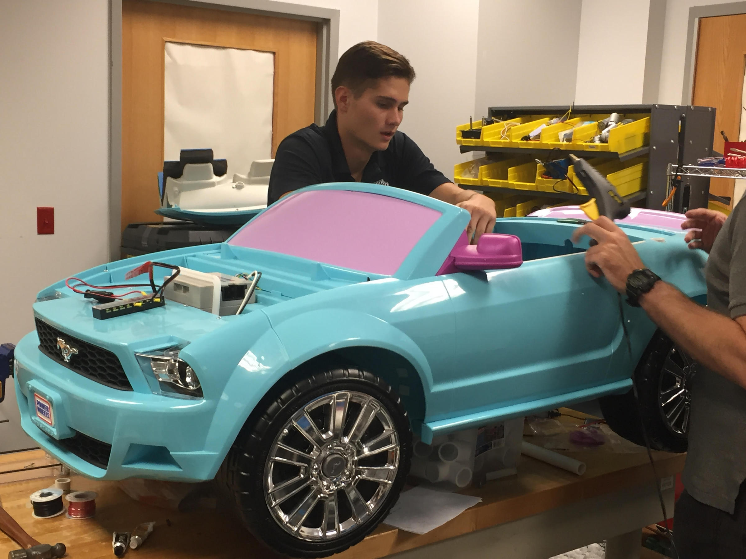unf mechanical engineering student kristian sipos works on a car for a young child with disabilities