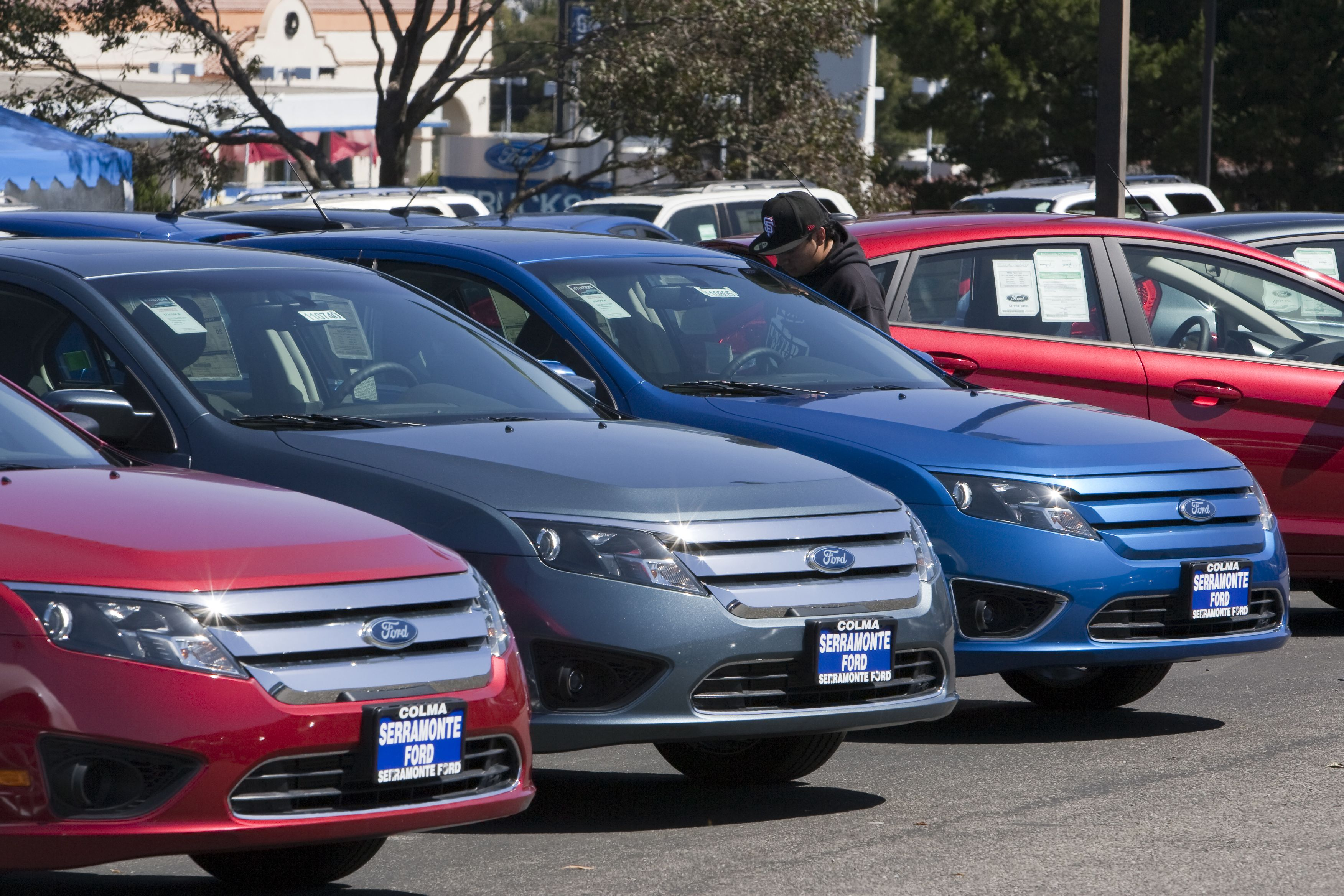 a customer looks over a ford fusion parked on the lot at a dealership in colma