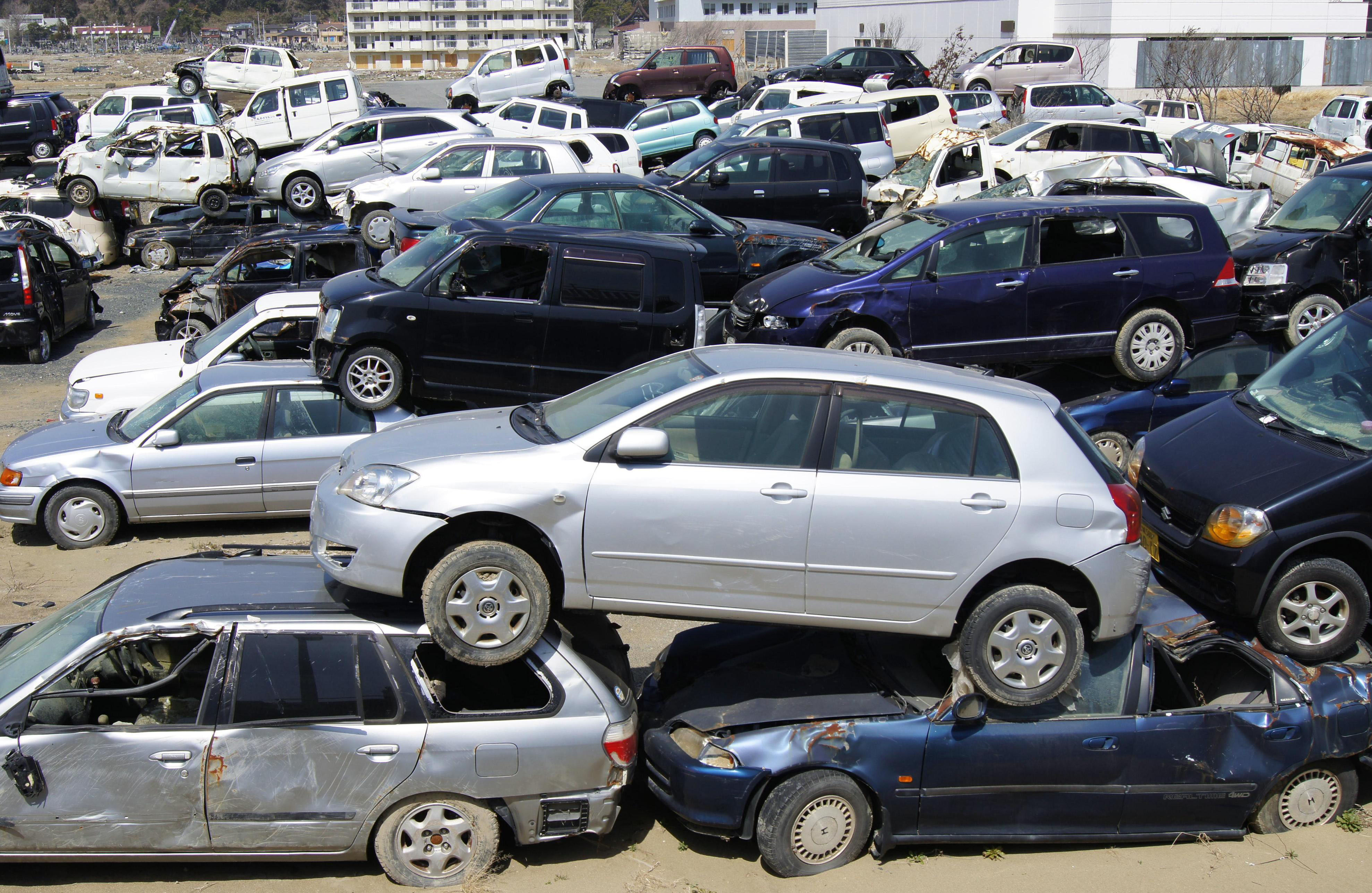 abandoned cars wrecked by last year s tsunami are piled up at a yard in ishinomaki