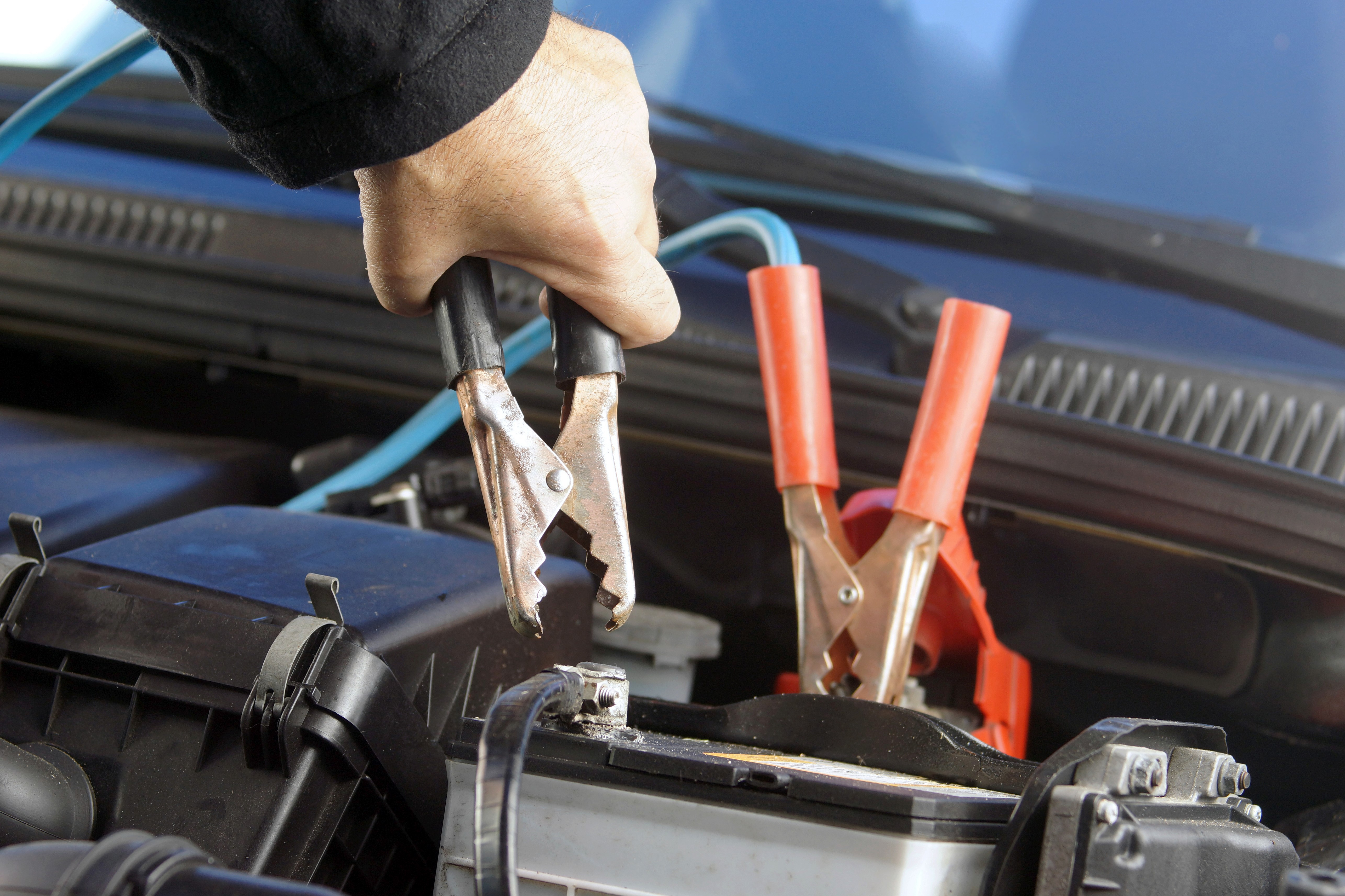a dead car battery being jump started