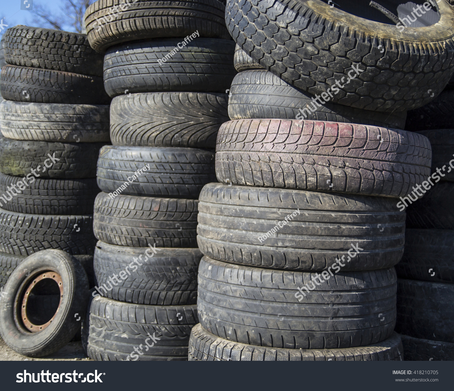a pile of used car tires stacked in a tower